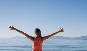 woman looking out to sea with arms spread wide