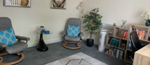 shotof inside therapy room with 2 chairs, desk, bookshelf
