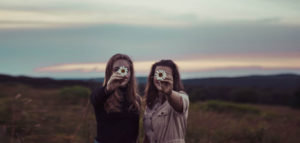 2 women holding daisies infront of their faces