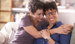 2 women hugging on sofa