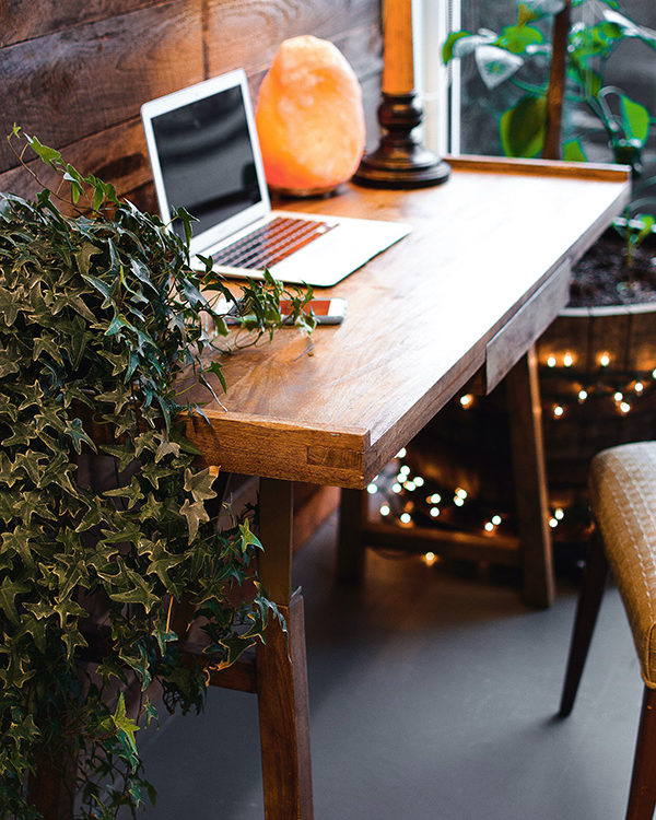 close p of wooden desk with plants, computer and salt lamp on