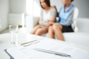 close up clipboard with therapist comforting women in background