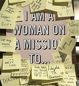 i am a woman on a mission too... sign with post-it notes stuck all around it