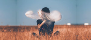 woman sat in field and motioning hands with clouds superimposed