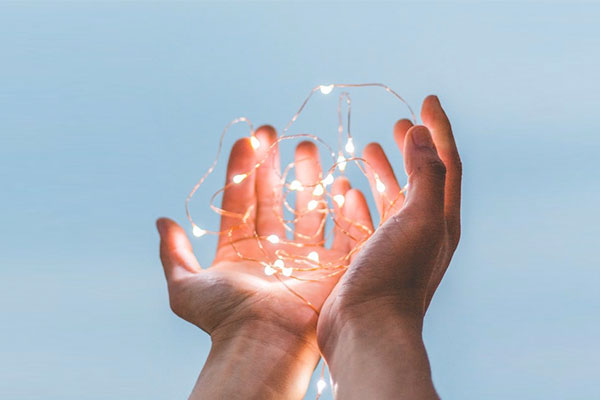 close up hands holding fairy lights
