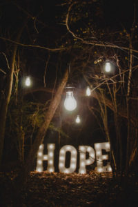 lights in a forrest spelling out hope