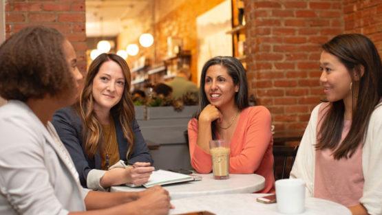 4 women in coffee shop chatting