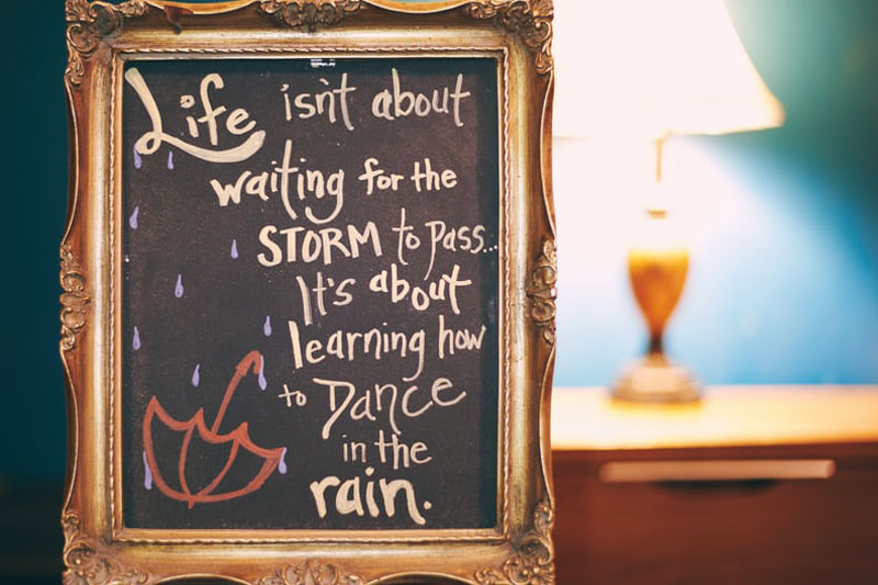 sign that says life isnt about waiting for the storm to pass but learning to dance in the rain