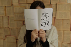 woamn holding book with pages outwards that read inctead of choosing merely to exist, I urge you to experience life, I urge you to live